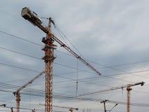 Drie gele bouwkraan tegen blauwe hemel Stock Fotografie
