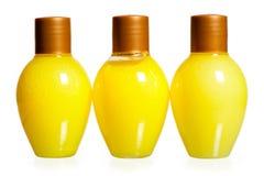 Drie gele flessen van schoonheidsmiddelen Stock Afbeelding