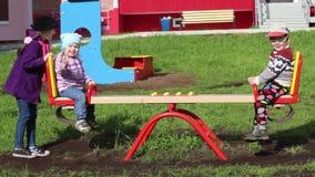 Drie gelukkig kinderenspel op geschommel bij zonnige de lentedag stock footage