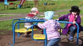Drie gelukkig kinderenspel op rotonde bij zonnige dag stock footage