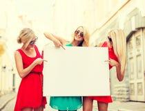 Drie gelukkige blondevrouwen met lege witte raad Stock Fotografie