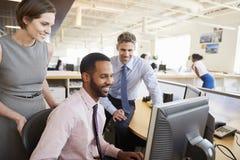 Drie gelukkige collega's die het computerscherm samen bekijken stock afbeeldingen