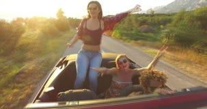 Drie gelukkige hipstervrienden die pret in convertibel hebben stock video