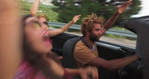 Drie gelukkige hipstervrienden op roadtrip in convertibele auto stock video