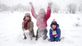 Drie gelukkige jonge geitjes die sneeuw op de winterlandschap werpen, langzame motie stock video