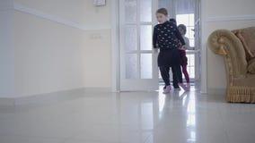 Drie gelukkige jonge geitjes openen de deur en stellen binnen grote lichte ruimte in werking De jongen en twee meisjes die in het stock video