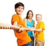 Drie gelukkige jonge geitjes trekken de kabel royalty-vrije stock foto