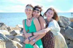 Drie gelukkige jonge hippiemeisjes die pret hebben bij het strand stock fotografie
