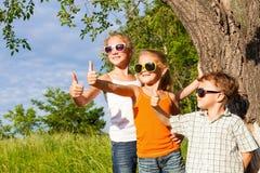 Drie gelukkige kinderen die dichtbij de boom in de dagtijd spelen Royalty-vrije Stock Foto