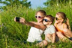 Drie gelukkige kinderen die dichtbij de boom in de dagtijd spelen Stock Afbeelding