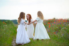 Drie gelukkige kinderen die handen en het spelen houden Stock Foto's