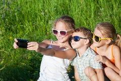 Drie gelukkige kinderen die in het park in de dagtijd spelen Royalty-vrije Stock Afbeeldingen