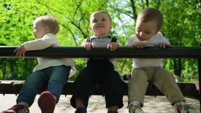 Drie gelukkige kinderen die op een bank in het park zitten stock videobeelden