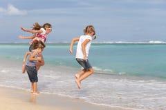 Drie gelukkige kinderen die op het strand spelen Royalty-vrije Stock Fotografie