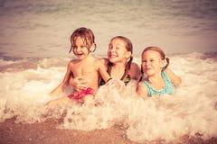 Drie gelukkige kinderen die op het strand spelen Royalty-vrije Stock Foto's