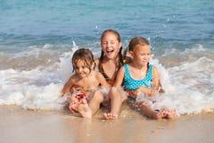 Drie gelukkige kinderen die op het strand spelen Stock Foto's