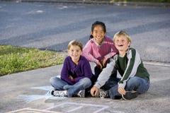 Drie gelukkige kinderen die op oprijlaan zitten stock foto's