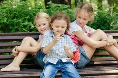 Drie gelukkige kinderen die in park spelen Royalty-vrije Stock Afbeeldingen