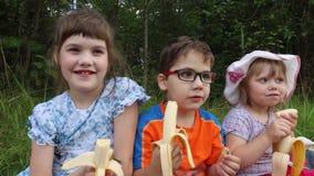 Drie gelukkige kinderen eten bananen stock video