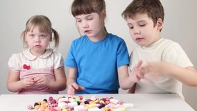 Drie gelukkige kinderen eten suikergoed en zitten bij lijst stock video