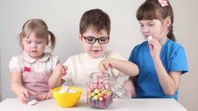 Drie gelukkige kinderen nemen heemst van kruik en eten op lijst stock videobeelden