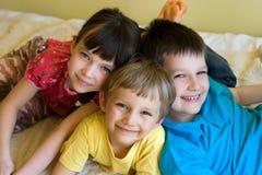 Drie gelukkige kinderen samen Stock Foto