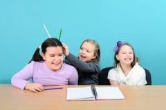 Drie gelukkige meisjes die grappen in school maken Stock Afbeelding