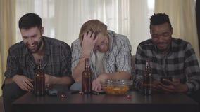 Drie gelukkige mensenvrienden die bij huis op cauch zitten, kijkend TV, het drinken bier met spaanders, die een videogesprek hebb stock videobeelden