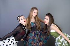 Drie gelukkige retro-gestileerde meisjes Stock Afbeelding