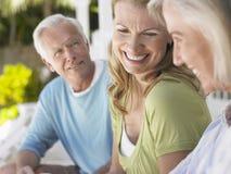 Drie Gelukkige Rijpe Mensen die op Veranda zitten royalty-vrije stock foto
