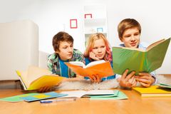 Drie gelukkige tienerjonge geitjes gelezen boeken die thuiswerk doen royalty-vrije stock afbeeldingen