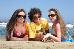 Drie gelukkige tieners op het strand Stock Foto
