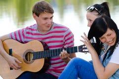 Drie gelukkige tienervrienden die gitaar in groen de zomerpark spelen Stock Foto's