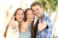 Drie gelukkige vrienden die met duimen omhoog in de straat glimlachen stock afbeeldingen