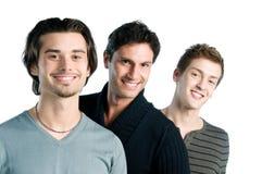 Drie gelukkige vrienden die zich verenigen Royalty-vrije Stock Afbeelding