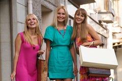 Drie gelukkige vrienden met zakken Stock Fotografie