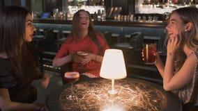 Drie gelukkige vrouwen die bij de kleine lijst in bar dicht omhoog zitten De meisjes hebben viering samen, en zij die babbelen gl stock footage