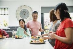 Drie Generatiefamilie die Diner hebben stock afbeeldingen