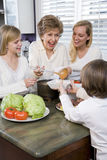 Drie generatiefamilie die in keuken lunch eet Stock Afbeeldingen