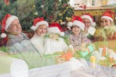 Drie generatiefamilie het openen Kerstmisgiften op laag Stock Foto