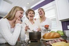 Drie generatiefamilie in keuken kokende lunch stock foto