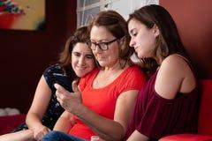 Drie generaties van Spaanse vrouwen die een smartphone bekijken royalty-vrije stock afbeelding