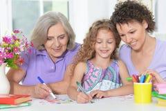 Drie generaties van vrouwen van één familie die thuiswerk doen Royalty-vrije Stock Foto