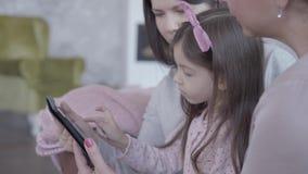 Drie generaties van vrouwen die samen in bank zitten, die en verklaren aan een klein grappig meisje hoe te om spel binnen te spel stock footage