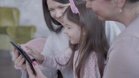Drie generaties van vrouwen die samen in bank zitten, die en verklaren aan een klein grappig meisje hoe te om spel binnen te spel stock videobeelden