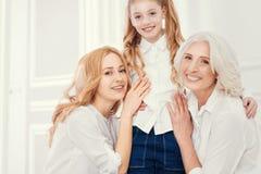Drie generaties van vrouwen die voor camera stellen stock afbeelding