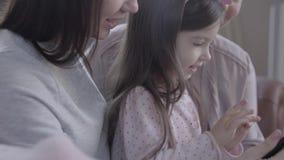 Drie generatiesvrouwen die samen in bank zitten, spreken letten en op hoe het kleine spel van het meisjesspel op tablet stock video