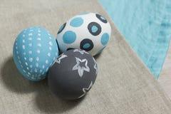 Drie geschilderde gekookte eieren op een grijs en turkoois servet Stock Foto's
