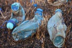 Drie gesmolten plastic flessen op het gebrande gras Royalty-vrije Stock Foto's