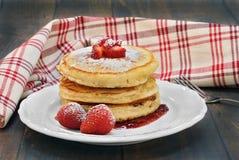 Drie gestapelde pannekoeken met verse aardbeien op een uitstekend hout Stock Afbeelding